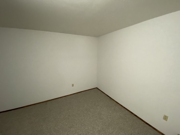 The corner of a room with bare walls.